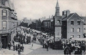 A busy clock tower with a coach outside the King's Arms